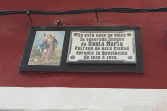 """The plaque on the wall in Carrer Pou that says """"in this house, the holy image of Santa Marta, patron saint of this town, was saved during the Revolution of 1936-9"""". In reality, it was the Nationalists, backed by the Catholic Church, that staged a revolt to overthrow the elected Republican government."""
