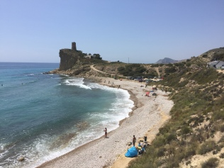 The shingle beach of Xarco with the watchtower at its end