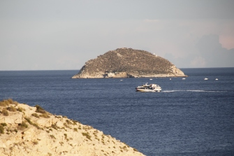 Isla de Benidorm. According to legend, it was cut from the summit of the Puig Campana mountain and rolled down into the bay.