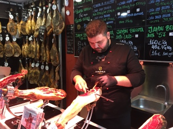 Slicing jamón ibérico clamped in a jamonera. Very fine slices with a thin-bladed flexible knife,